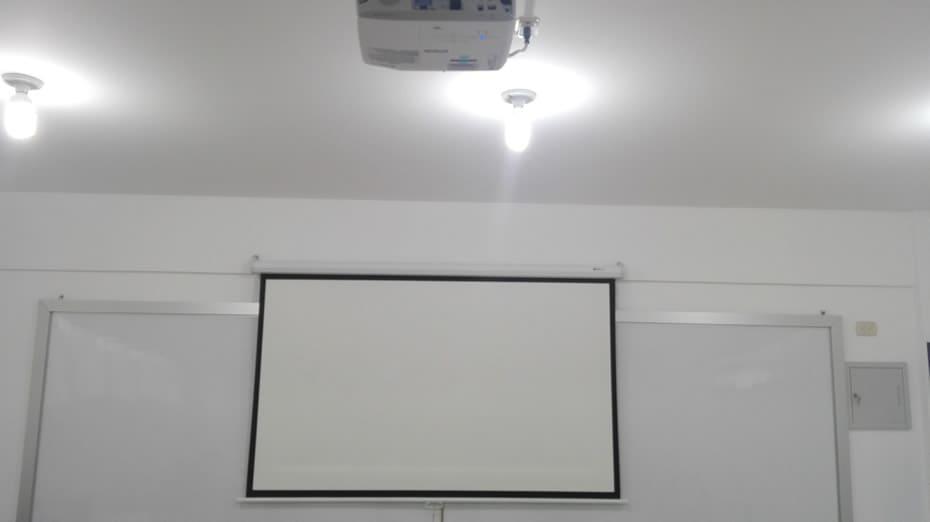 Proyector enfocado y haciendo prueba de proyección en ecran, calculando posición, distancia y enfocado